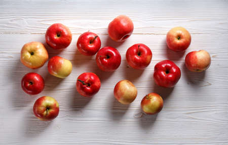 red apples scattered on a white wooden table, flat lay