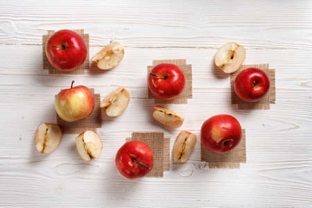 red apples on a white wooden table, flat lay
