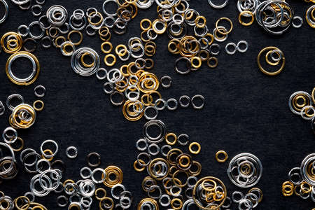 round metal links for jewelry making, connecting rings for chains scattered on a black background Reklamní fotografie