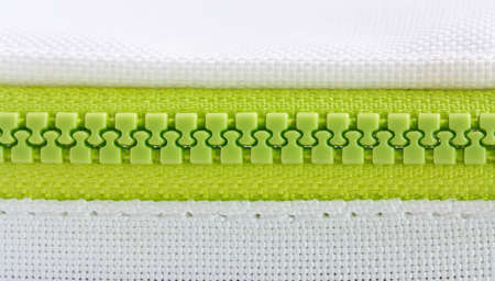 bright green plastic zipper sewn in white cloth