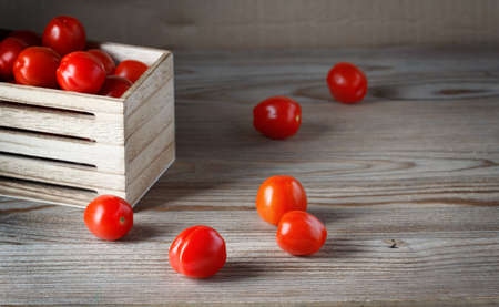 red Cherry tomatoes in a wooden box, scattered on a table