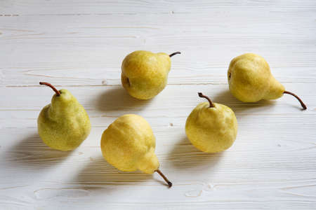 yellow pears pham scattered on a white wooden table, top view