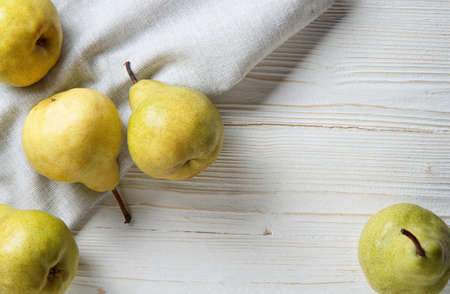 yellow pears pham scattered on a white wooden table on a linen kitchen towel, flat lay