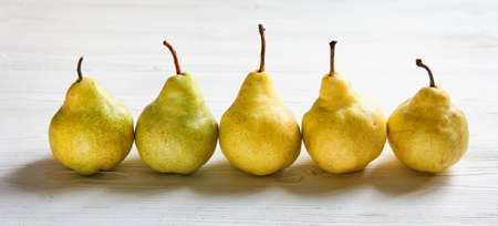 Yellow pakham pears standing in a row on white table