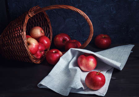 red apples on a wooden table on a linen napkin are scattered from the basket, low key, still life