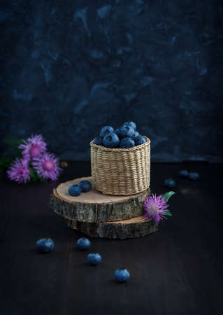blueberries in wicker box on a wooden table, rustic still life