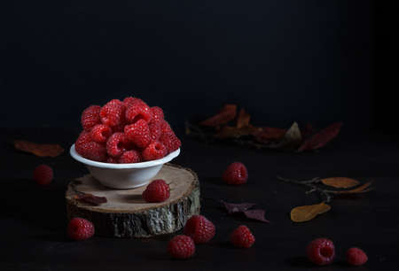 fresh ripe raspberries in a bowl on a black background, rustic still life