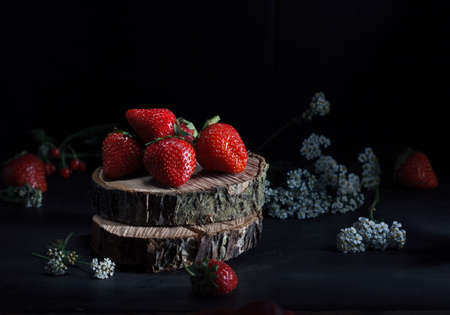 fresh ripe strawberries in a bowl on the stump cuton on black background