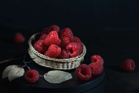 fresh ripe raspberries in a wicker bowl on a black background