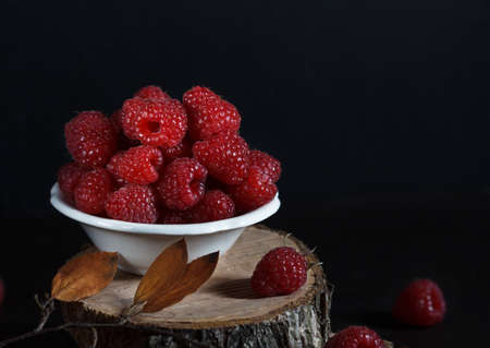 fresh ripe raspberries in a bowl on the stump cuton on black background 免版税图像