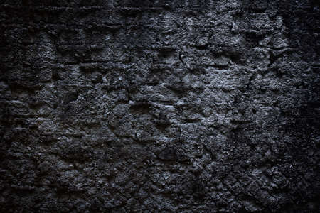 black brick wall covered with cement
