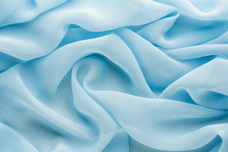 light blue fabric draped with large folds, delicate textile background