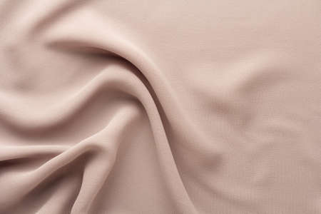 flesh-colored fabric draped with large folds, textile background