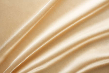 light shiny golden fabric draped with large folds, textile background