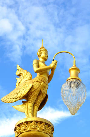 A golden Kinnara (The male counterpart of Kinnari) with lamp Stock Photo - 10360485