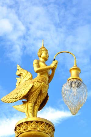 A golden Kinnara (The male counterpart of Kinnari) with lamp Stock Photo - 10360485