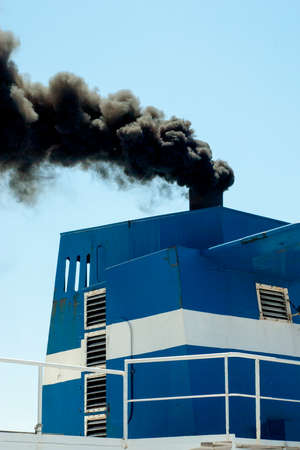 departing ship with smoke emission and air pollution photo