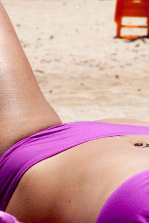 navel piercing: female body in swimsuit sunbathing with custom pink and navel piercing