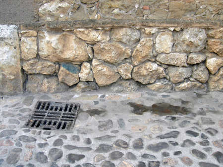Particular of a wall of mud bricks with some little stones and straw and concrete bricks in edge and a street of stones with well of the sewer photo