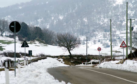a snowy landscape mountains, road signs, trees, cleaned road photo