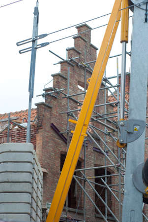 construction site with equipment and material in front of and behind red brick facade photo