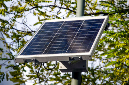 sustainable small solar panel with branches and leaves of trees in the background for the environment photo