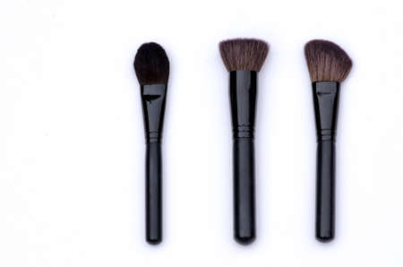 bristles: set of three professional make up  brushes for the face with black handle metal and dark bristles on white background