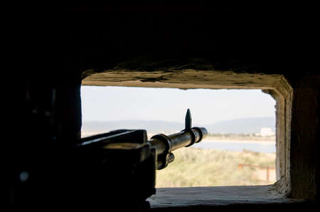 embrasure: rifle ready to shoot in the embrasure in background made from landscape with lake and green as a photo
