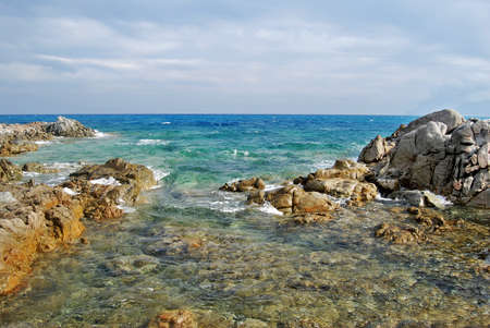 agitated: Sunny coastal landscape with rocks, agitated sea and cloudy sky for tourism Stock Photo
