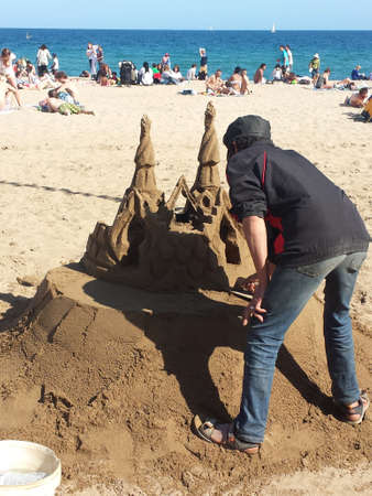 elaborate: Unidentified man who builds an elaborate sand castle at the beach Editorial