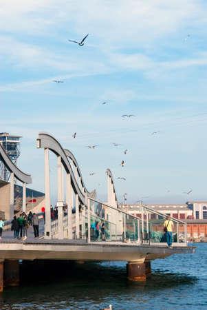 rambla: Barcelona, Spain - APRIL 08: Rambla de Mar, a modern bridge in the Barcelona port area with people and birds on April 08.2014 in Barcelona, Spain as editorial