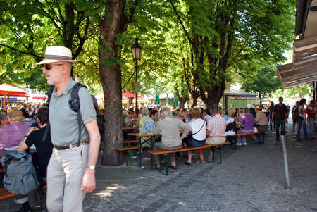 biergarten: Munich, Germany -July 07: People having lunch outdoor under the trees in the square in a sunny day on July 07.2011 in Munich, Germany as editorial