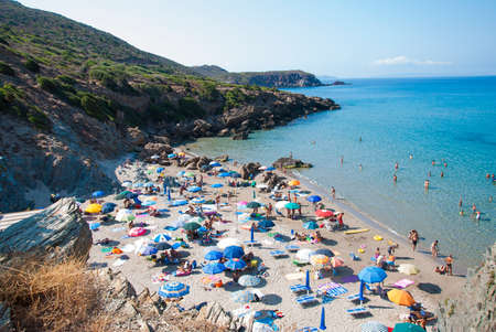 Masua Beach, Italy - August 19: Masua Beach in Nebida crowed in summertime seen from the top eith blue sea on August 19.2013 in Masua, Italy as editorial