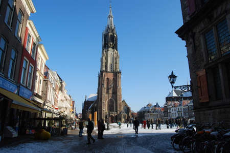 delft: Delft, Netherlands - January 31: daily and snowy main square of Delft in the Netherlands in the morning with people and blue sky as lifestyle on January 31, 2010 in Delft, Netherlands as editorial