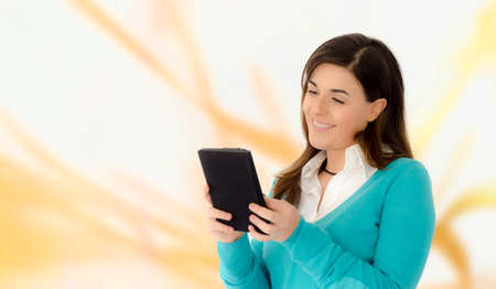 e book device: Caucasian beautiful girl smiling reading on a table portrait on orange abstract background