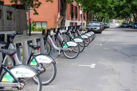 shared sharing: Montreal, Quebec, Canada - 18 July 2016 - Shared bikes are lined up in the streets of Montreal, Quebec. First large-scale in North America city public bicycle sharing system Bixi, launched in May 2009, has over 400 stations and 5000 bikes. Bicycles in bik