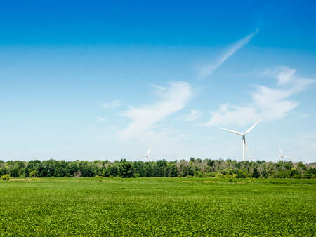 Wind Turbine in a green level field and deep blue sky and some clouds Stock Photo