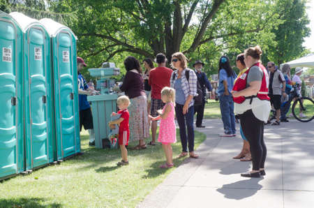 London Ontario, Canada - July 16, 2016: Children waiting with their mom for street bio-toilet in the park (Victoria Park) during the country festival as editorial