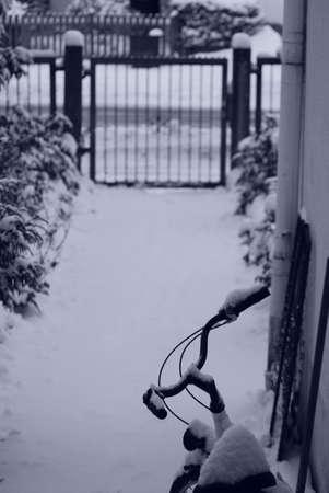 Snow - covered bike in the walkway during wintertime. Monocolor effect Zdjęcie Seryjne