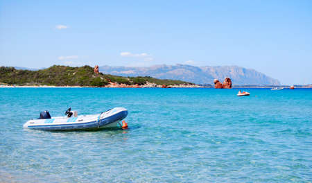 white rubber boat in the clear blue sea and mountains in the background for tourism in sardinia