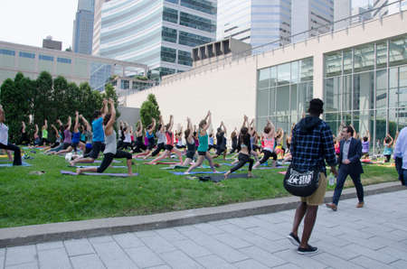 Montreal, Quebec, Canada - 20 July 2016 - A group of women practing yoga in a class in a green area in the center of the city with people walking on the sidewalk during summertime as editorial