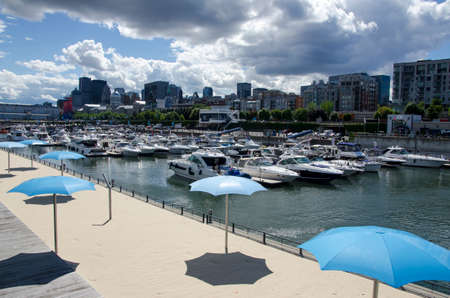 Montreal, Quebec, Canada- July 19 2016: White yachts in the port waiting during summertime. An artificial beach in the front and city/buildings in the background as editorial