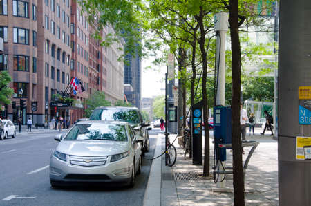 Montreal, Quebec, Canada - 20 July 2016: Electric car charging at recharging station in the street under green trees in summertime as editorial