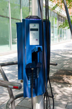 Montreal, Quebec, Canada - 20 July 2016: Recharging station for electric cars in the street under green trees in summertime as editorial