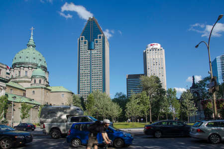 Montreal, Quebec, Canada - 18 July 2016 - Buildngs and heavy traffic in downtown in Montreal in summertime. Canadian lifestyle with cars, people and skyscapers as editorial
