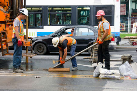 Montreal, Quebec, Canada- July 19 2016 - road repair laborers crew with heavy machinery working in the center of the street as editorial
