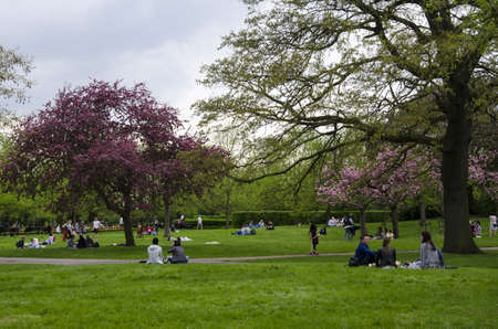 London, UK. 22th April 2018. People getting rest in a cloudy park in Regent Park as editorial Publikacyjne