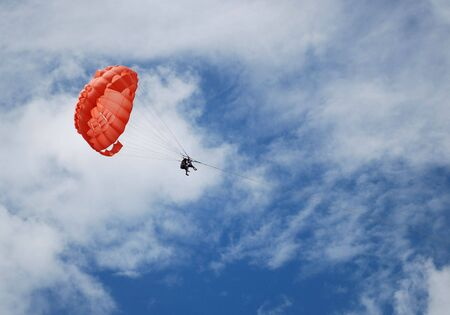 parachutists: Two persons parasailing through the air with a red parachute