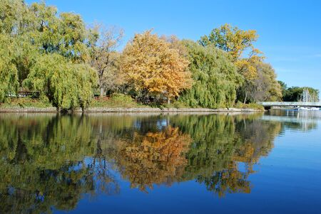 Reflection of autumn trees in blue water, Ontario, Canada Stock Photo