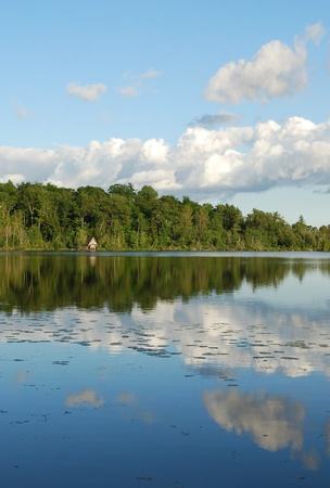 Forest and clouds reflection in lake, Ontario, Canada